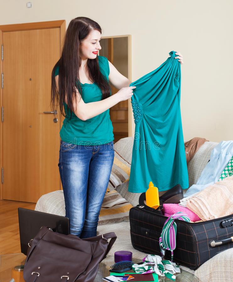 Kvinna som väljer klänningen för semester arkivfoton
