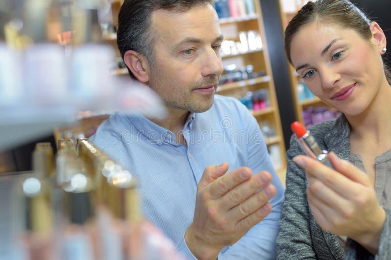 Kvinna som väljer läppstift i kosmetiskt lager arkivbilder