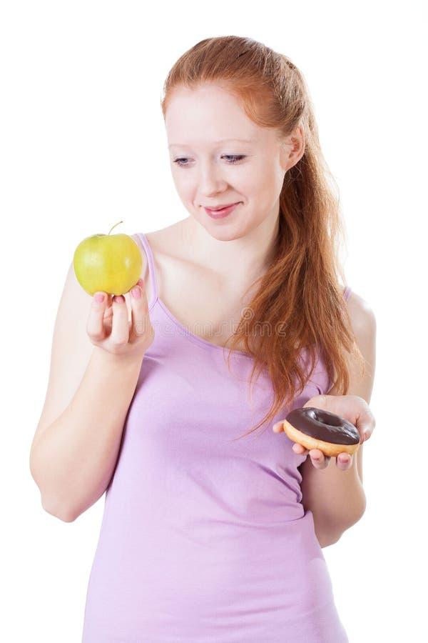Kvinna som väljer mellan frukter och sötsaker royaltyfri fotografi