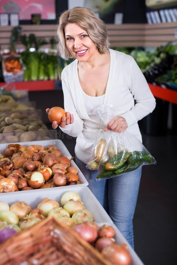 Kvinna som väljer veggies i livsmedelsbutik arkivfoton