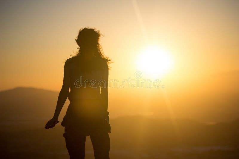 Kvinna som vänder solnedgången mot royaltyfri bild