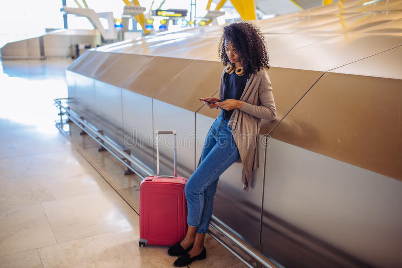 Kvinna som väntar hennes flyg genom att använda mobiltelefonen på flygplatsen fotografering för bildbyråer