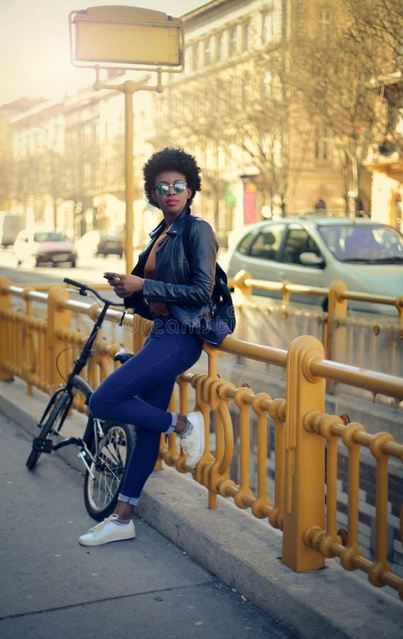 Kvinna som väntar med hennes cykel arkivbild