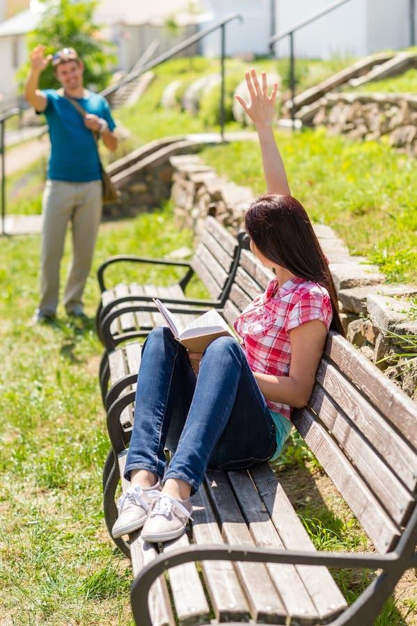 Kvinna som vågr för att man att sitta på bänk royaltyfri bild