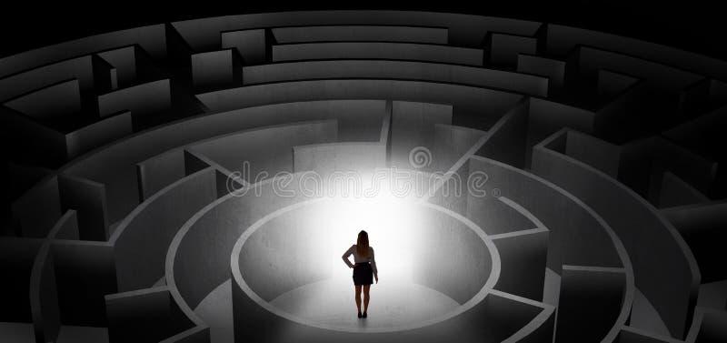Kvinna som v?ljer mellan ing?ngar i en mitt av en m?rk labyrint royaltyfria foton