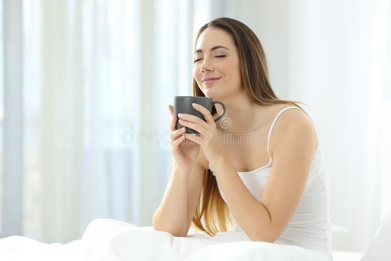 Kvinna som vaknar tycka om upp en kopp kaffe på sängen royaltyfria foton