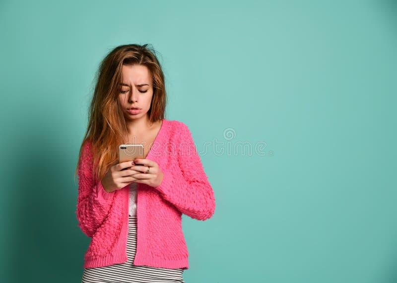 Kvinna som ?verf?r ett textmeddelande p? en mobiltelefon arkivfoto