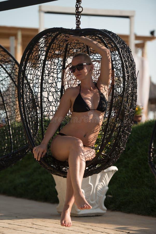 Kvinna som vilar i en hängande korg för metallrotting arkivfoton