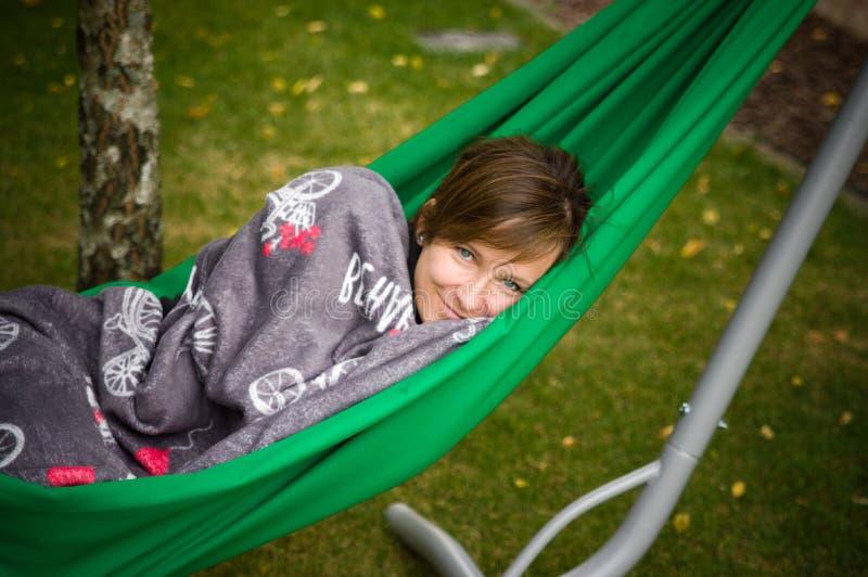 Kvinna som vilar i grön hängmatta royaltyfri bild