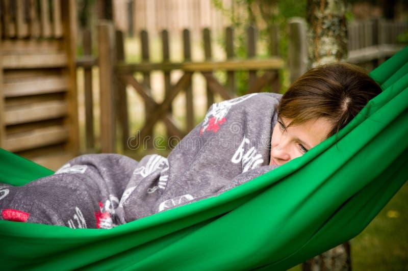 Kvinna som vilar i grön hängmatta arkivbild