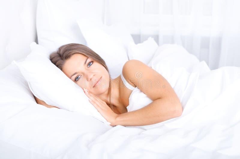 Kvinna som vilar i säng royaltyfri fotografi