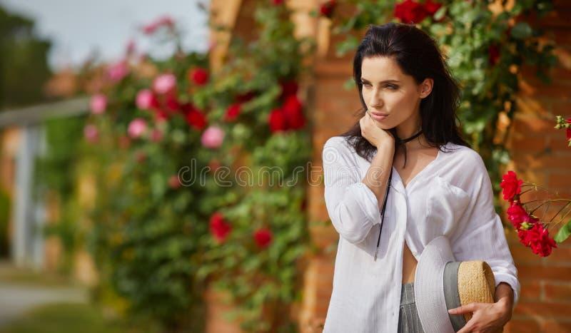 Kvinna som vilar i sommaren den italienska trädgården royaltyfria bilder