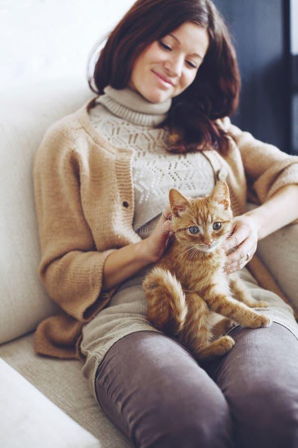 Kvinna som vilar med kattungen fotografering för bildbyråer