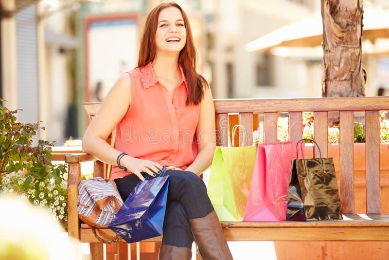 Kvinna som vilar med shoppingpåsar som sitter i galleria arkivfoto