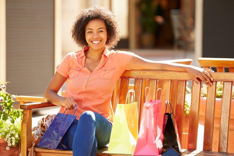 Kvinna som vilar med shoppingpåsar som sitter i galleria fotografering för bildbyråer