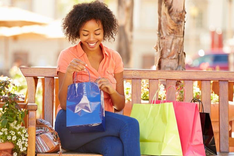 Kvinna som vilar med shoppingpåsar som sitter i galleria royaltyfria bilder