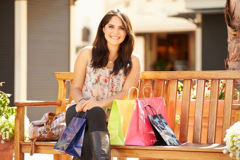 Kvinna som vilar med shoppingpåsar som sitter i galleria arkivbilder