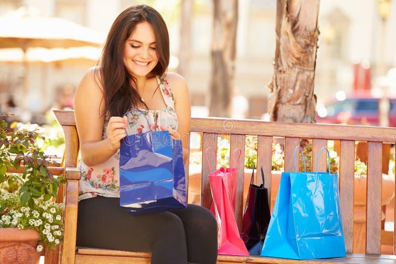 Kvinna som vilar med shoppingpåsar som sitter i galleria arkivbild