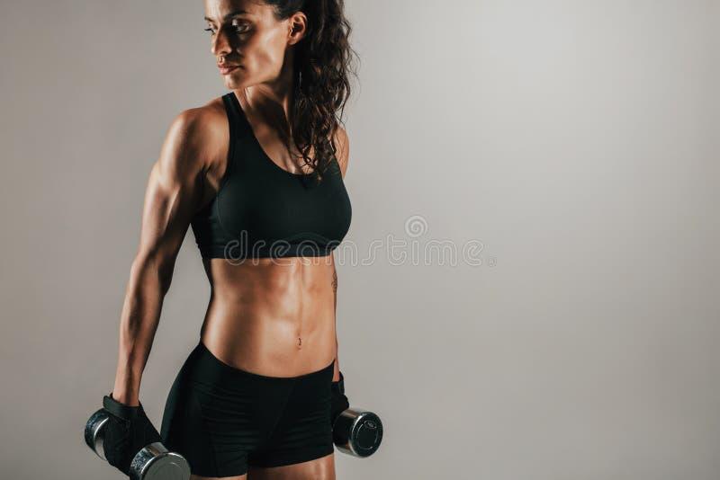 Kvinna som vilar vikter på hennes sidor, medan se arkivfoton
