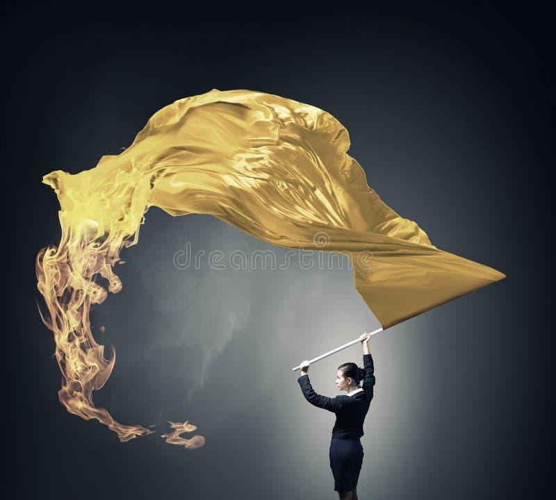 Kvinna som vinkar den gula flaggan Blandat massmedia royaltyfri foto
