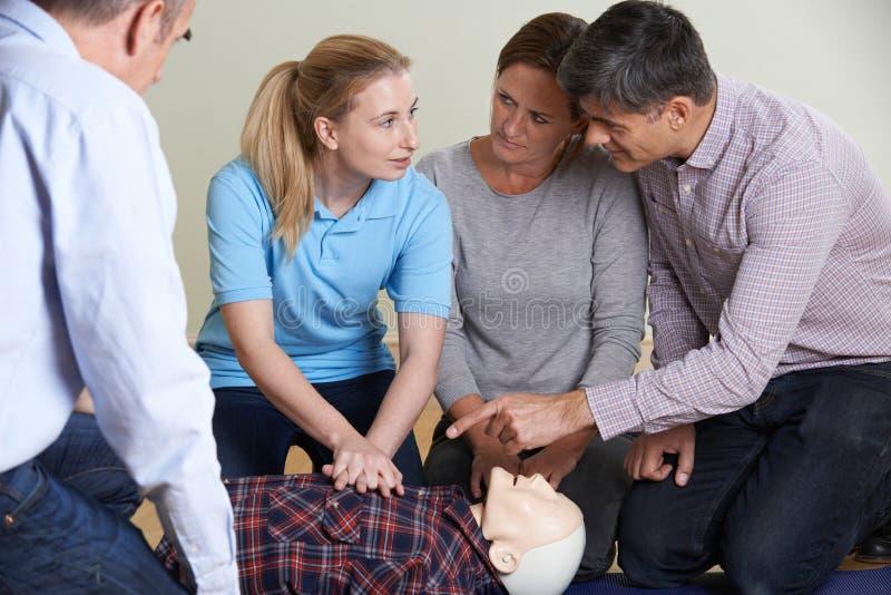 Kvinna som visar CPR på utbildningsattrapp i första hjälpengrupp royaltyfria foton