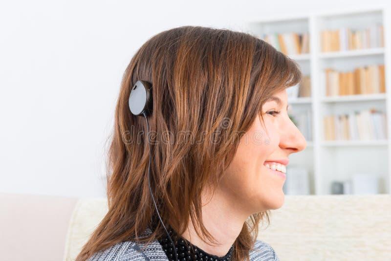 Kvinna som visar den cochlear implantatet arkivbild