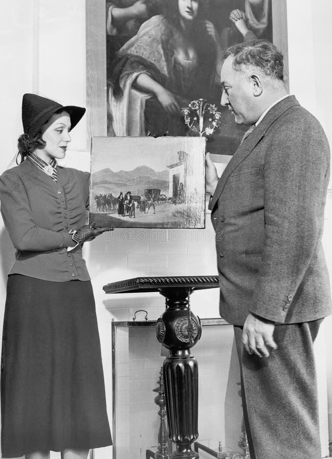 Kvinna som visar en äldre man per stycke av konst (alla visade personer inte är längre uppehälle, och inget gods finns Leverantör royaltyfria bilder
