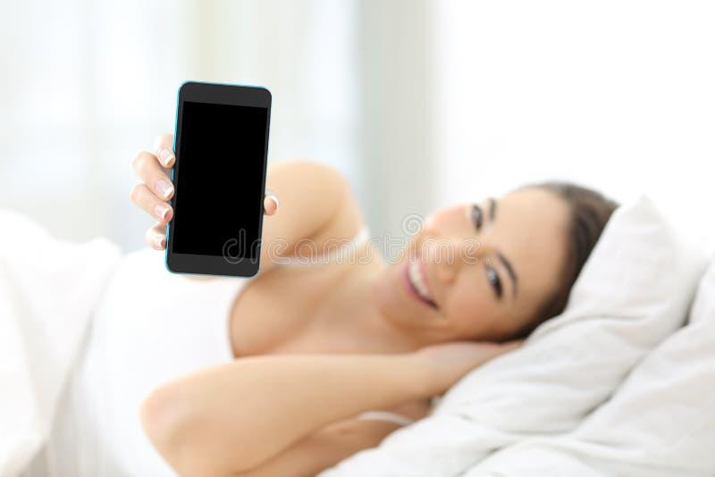 Kvinna som visar en smart telefonskärm på sängen royaltyfri fotografi