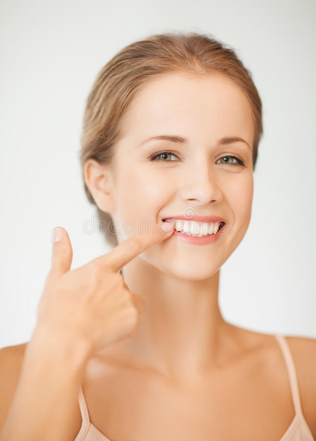 Kvinna som visar hennes tänder arkivfoton