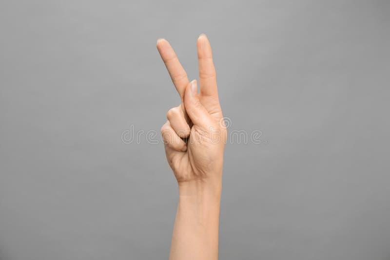 Kvinna som visar K-bokstaven på grå bakgrund Teckenspråk fotografering för bildbyråer