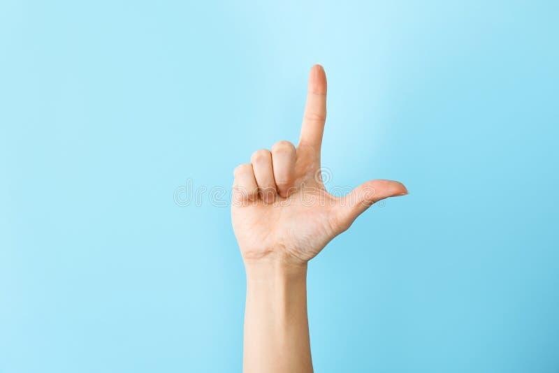 Kvinna som visar L bokstav på färgbakgrund Teckenspråk fotografering för bildbyråer