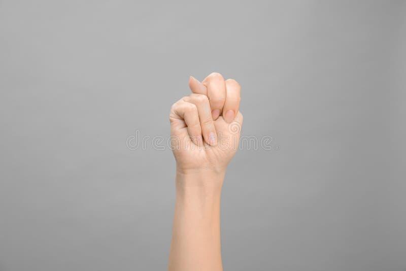 Kvinna som visar n-bokstaven på grå bakgrund Teckenspråk fotografering för bildbyråer