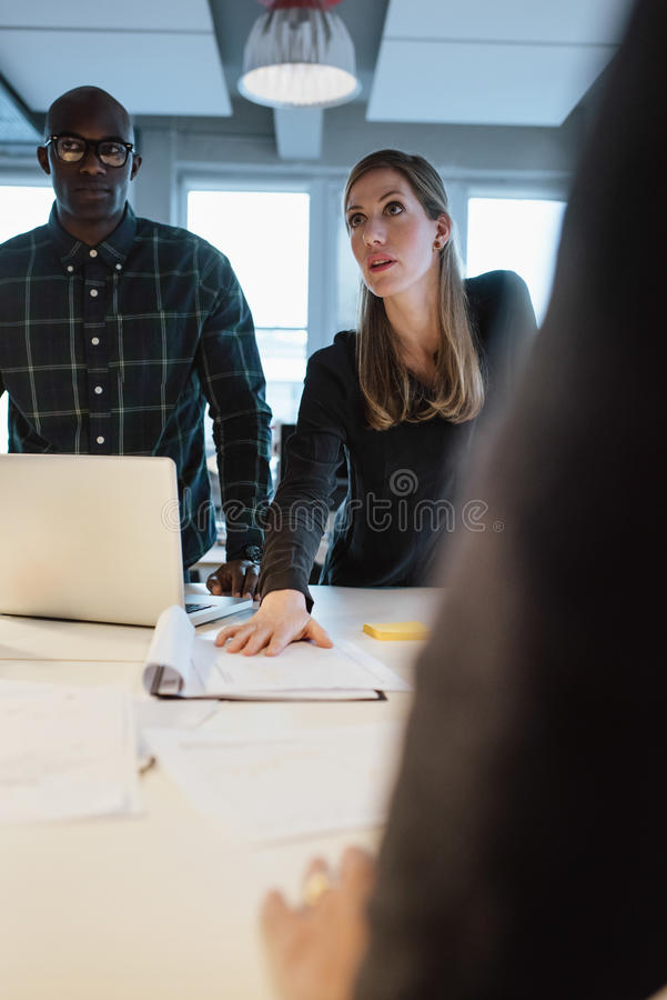 Kvinna som visar nytt affärsförslag till coworkers arkivbild