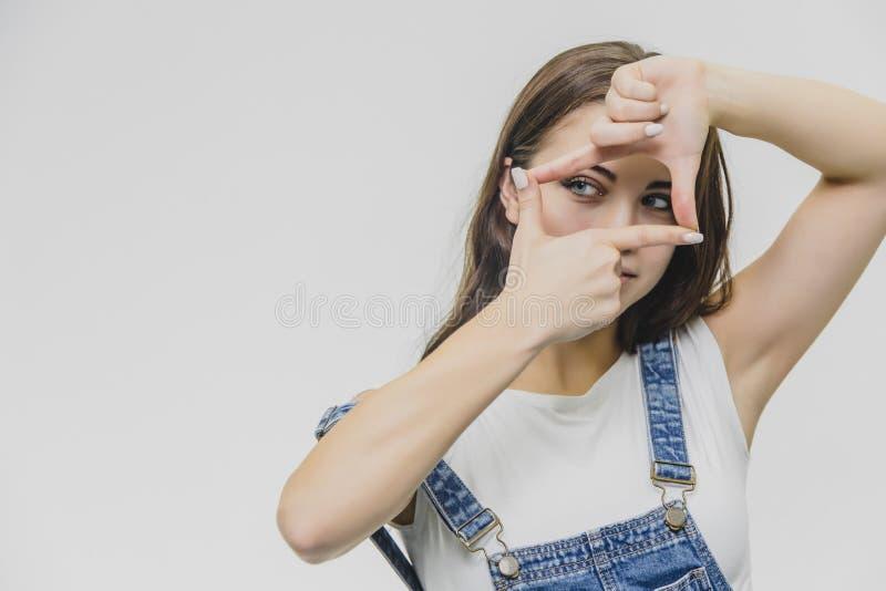 Kvinna som visar ramfingertecknet Ung kvinna som inramar sig med händer bakgrund isolerad white fotografering för bildbyråer