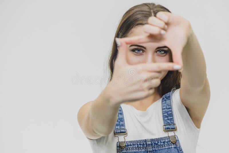 Kvinna som visar ramfingertecknet Ung kvinna som inramar sig med händer bakgrund isolerad white arkivfoto