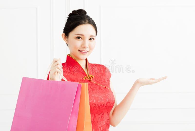 Kvinna som visar shoppingpåsarna och introducerar något royaltyfria foton