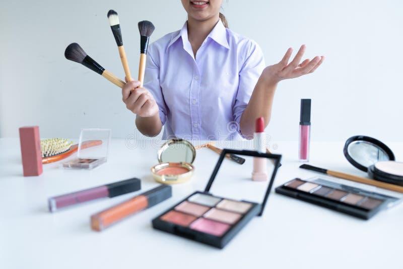 Kvinna som visar skönhet den kosmetiska produkten och TV-sändning till det sociala nätverket vid internet, begrepp för skönhetblo royaltyfria foton