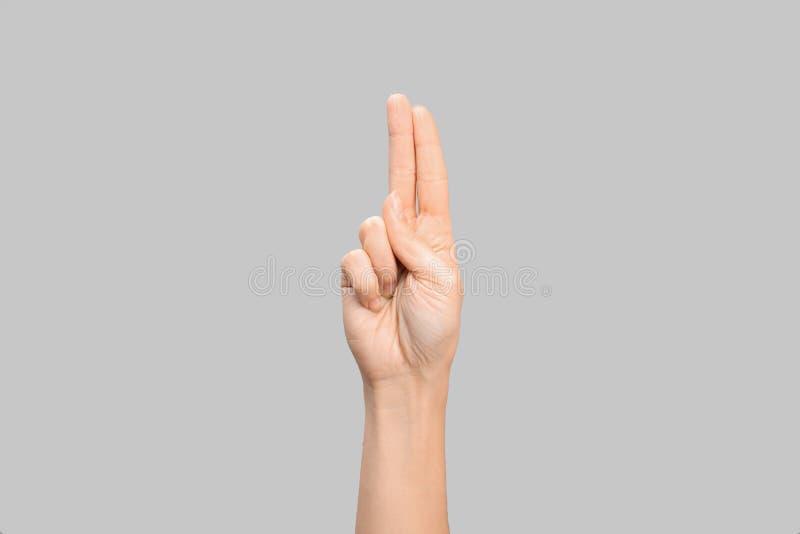 Kvinna som visar U-bokstaven på grå bakgrund Teckenspråk arkivfoto