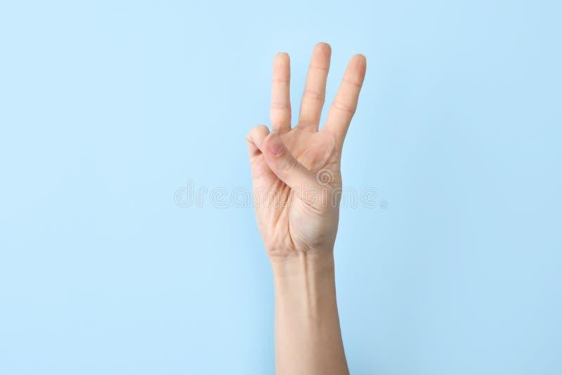 Kvinna som visar W-bokstaven på färgbakgrund Teckenspråk arkivfoto
