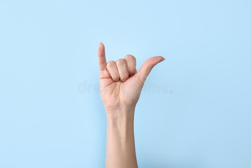 Kvinna som visar y-bokstaven på färgbakgrund, closeup arkivfoton
