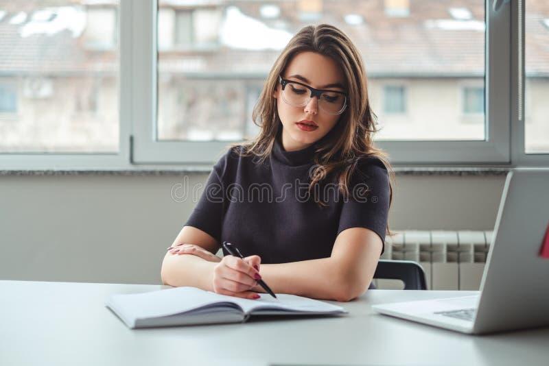 Kvinna som vrida sig i hennes anteckningsbok på kontoret royaltyfri fotografi