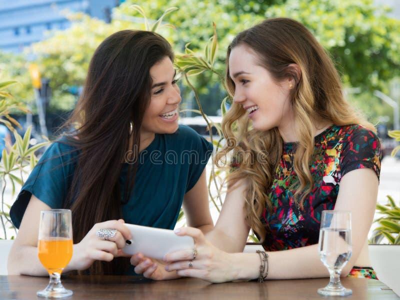 Kvinna två med telefonen på restaurangen royaltyfri foto