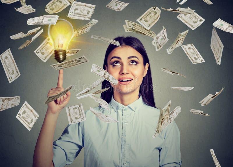 Kvinna under pengarregn som pekar upp på den ljusa kulan för idé royaltyfri bild