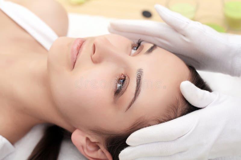 Kvinna under yrkesmässig ansikts- massage i skönhetbrunnsort arkivbild