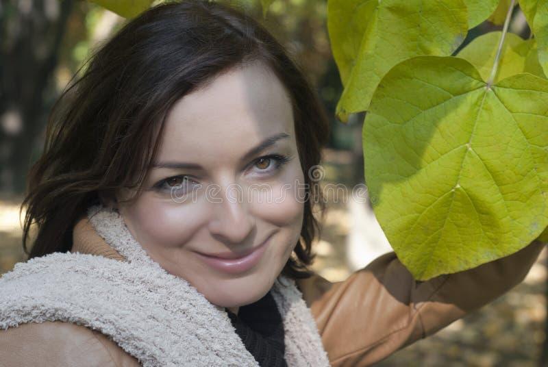 Kvinna utomhus under gröna leaves royaltyfri foto