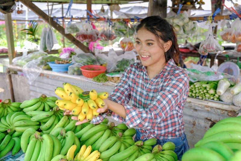Kvinnaaffärsmannen säljer grönsaker, frukter, och bananer, som är moget gult i en lantlig vägren, shoppar Thailand fotografering för bildbyråer