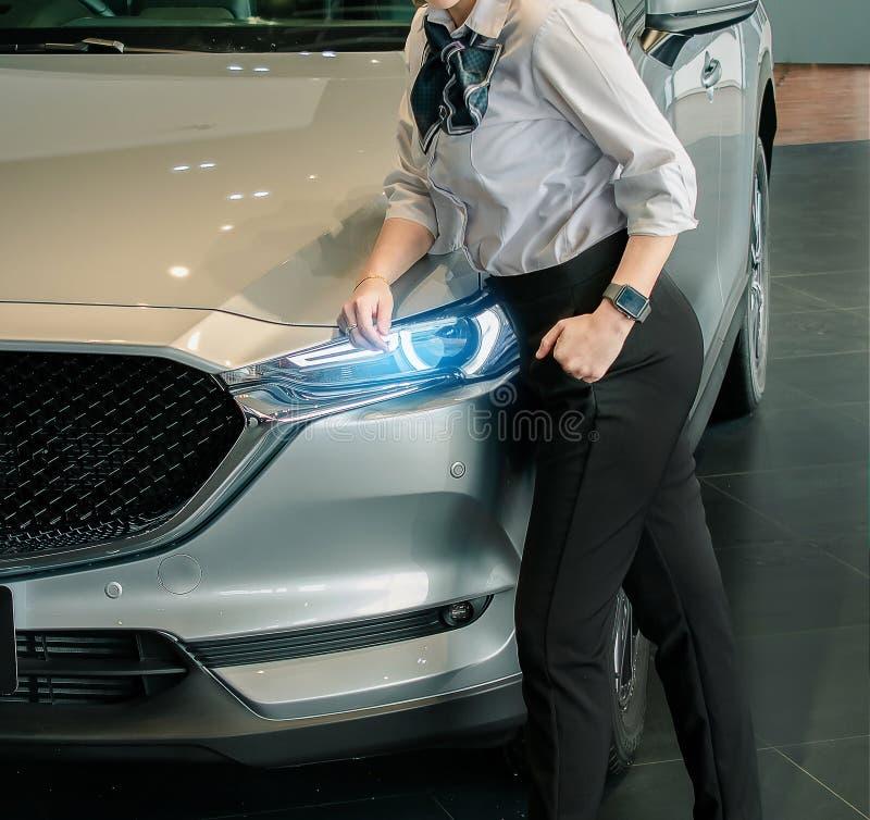 Kvinnaaffärssaleman med bilen i suddig bakgrund för visningslokalkontor F?r automatisk bil- eller transporttrans.bild arkivbild