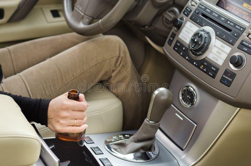 Kvinnaalkoholist med en flaska av fyllan i bilen royaltyfri fotografi
