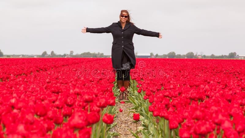 Kvinnaanseende i ett fält av tulpan arkivbilder