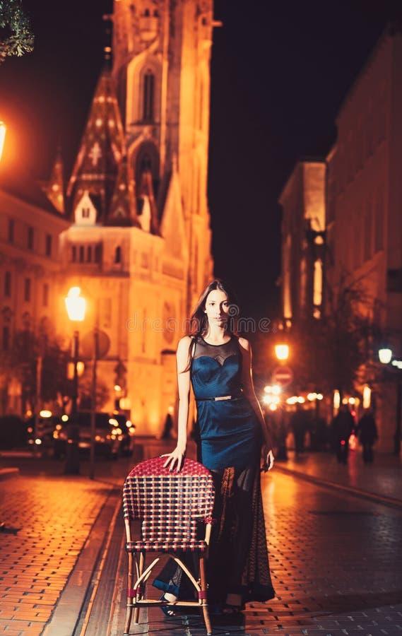 Kvinnaanseende i gatan som ser staden p? natten med stol arkivbild
